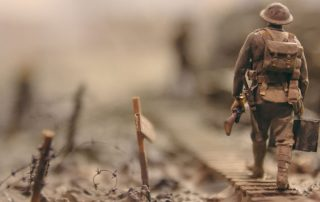 A soldier is walking on field with armor.