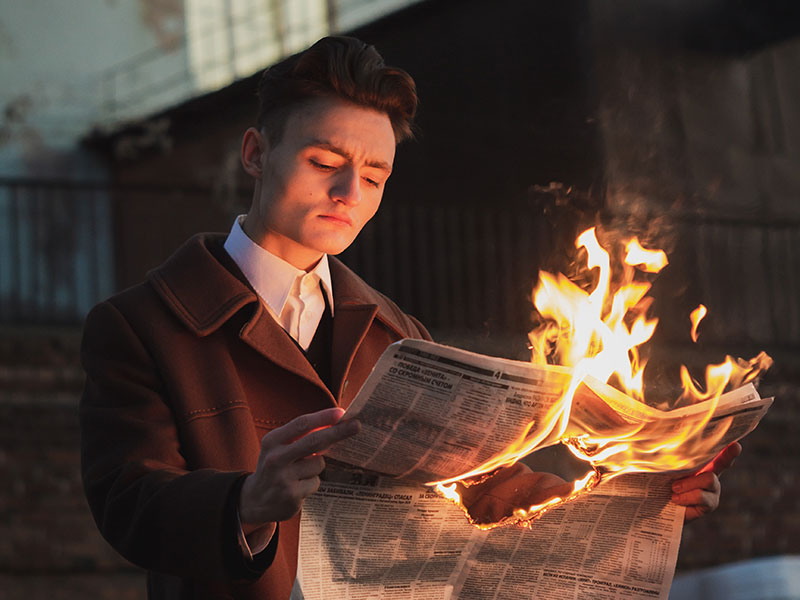 A man is reading newspaper confidently which is burning.